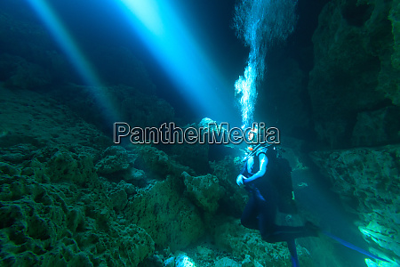 sunrays shine on scuba diver in