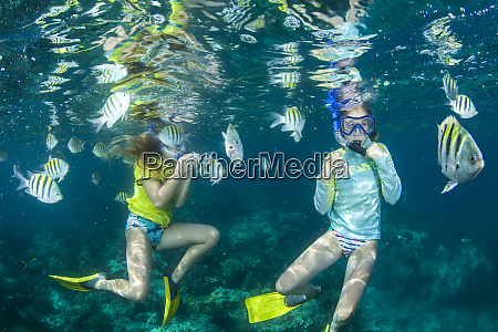 young girls snorkeling with tropical fish