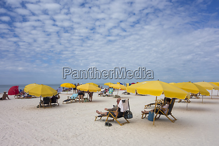 people sitting on beach chairs under