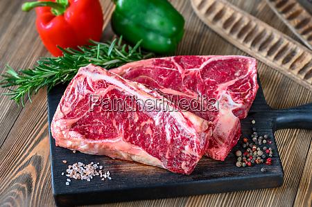 raw beef steaks with seasonings