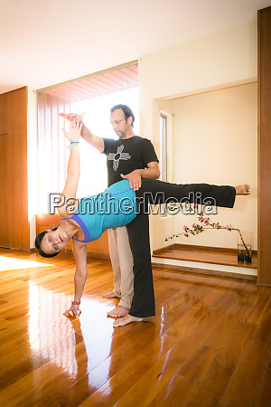 yoga instructor assisting a student during