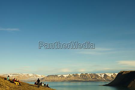 arctic svalbard lomfjorden tourists sit to