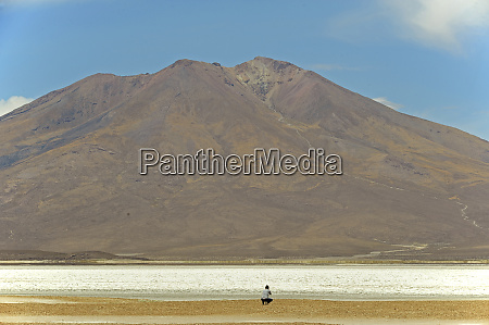photographer taking picture below mountain coipasa