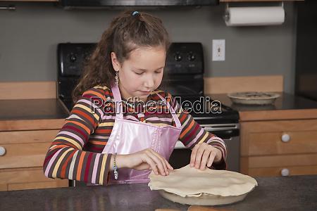 girl placing top pie crust on