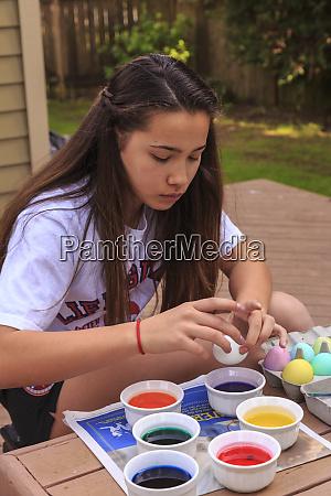 teenage girl coloring easter eggs