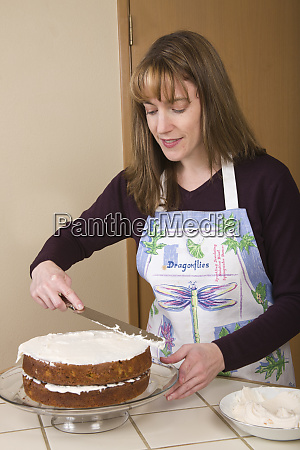 woman frosting a carrot cake on
