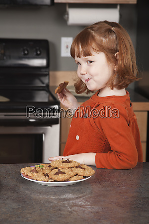 girl eating freshly baked cookie mr