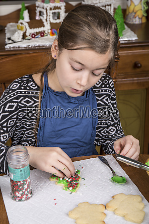 girl putting candy sprinkles on a