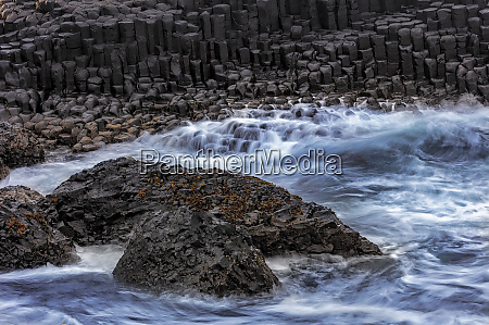 waves crash into basalt at the