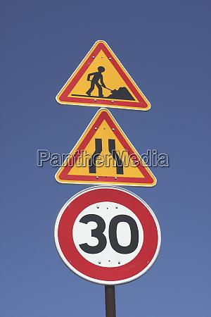 road sign road narrows 30 kmph