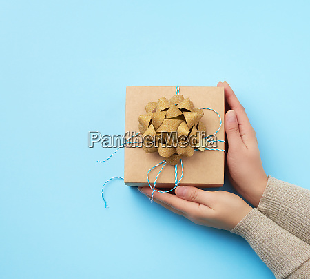 female hand holds a square box