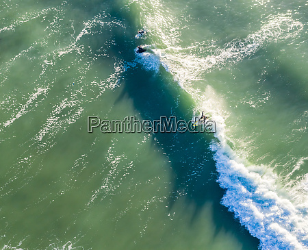aerial view of surfer catching waves