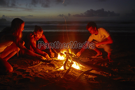 family toasting marshmallows on the beach