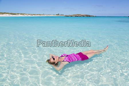 bahamas little exuma island woman floating