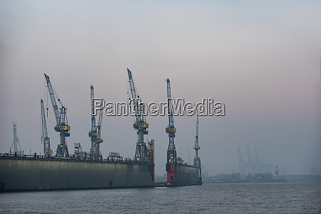 docks of hamburg harbor with cranes