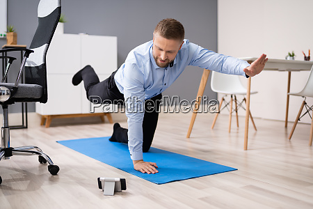 businessman doing stretching workout using smartphone