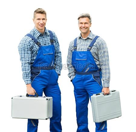 portrait of two repair men holding