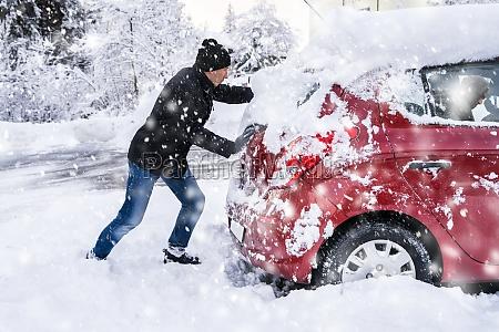 man pushing a car stuck in