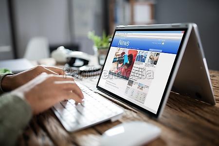 businessman reading news on laptop at