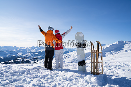 young couple standing near snowboard and