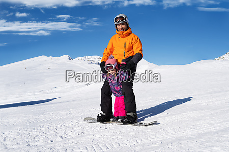 father riding snowboard with his daughter