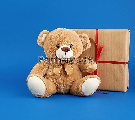 beige teddy bear and a box
