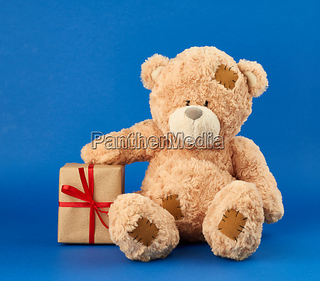 large beige teddy bear holds a