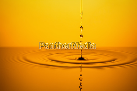 golden oil drops on yellow background