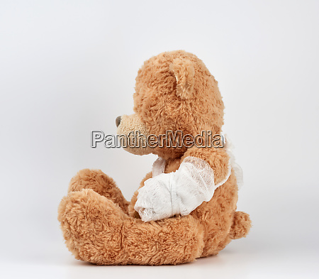 large beige teddy bear with patches