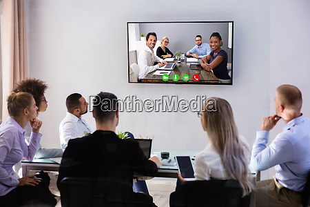 businesspeople video conferencing in boardroom
