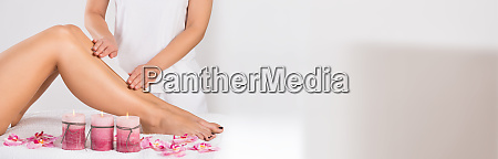 beautician waxing womans leg at salon