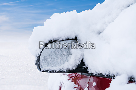 car mirror covered with snow