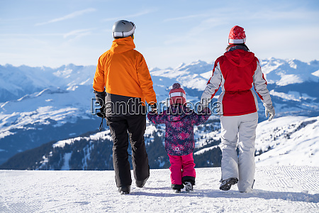little girl walking with her parents