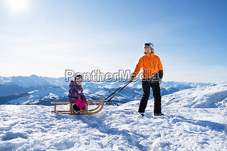man pulling his daughter on wooden