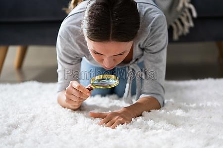 woman looking at carpet through magnifying