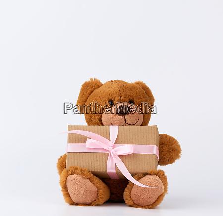 cute little brown teddy bear holds