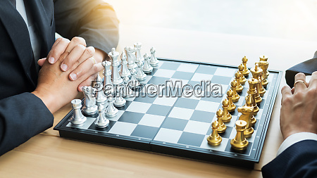 businessman playing chess game figures on