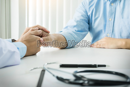 male doctor holding patients hand comforting
