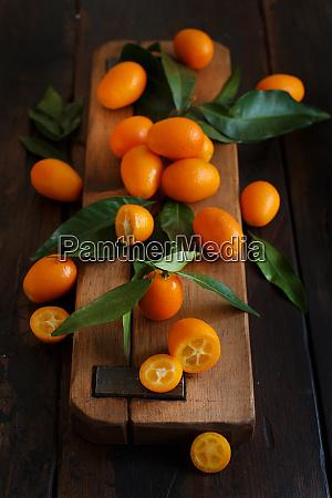 kumquat fruits on a dark wooden