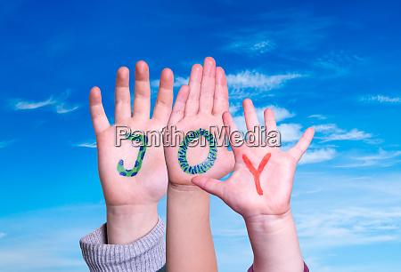 children hands building word joy blue