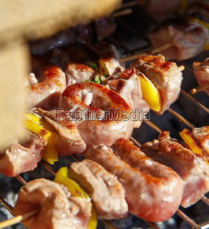meat and sausages skewers cooking on