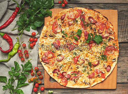 baked round pizza with smoked sausages