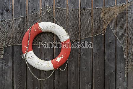 old lifebelt and fishing net hanging