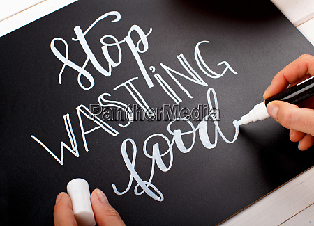 woman writing on a chalkboard stop