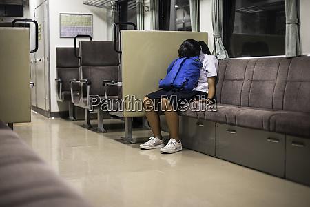 japan tokyo schoolgirl resting on train