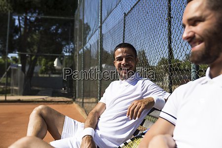 tennis players sitting on a bench