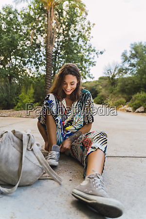 laughing young woman sitting on slab
