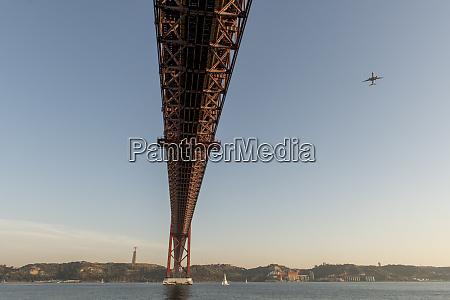 plane above 25th of april bridge