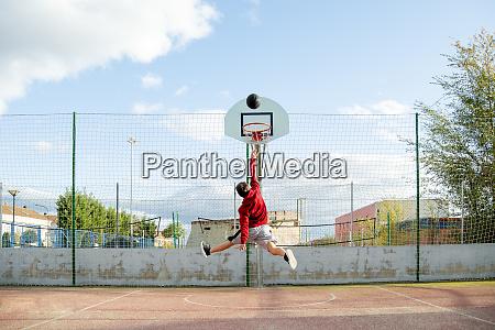 teenager playing basketball dunking