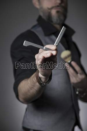 barber showing a straight razor in